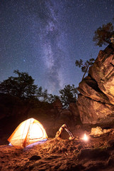 Campsite at night amid huge steep rock formations. Athletic slim girl doing yoga exercises at small tourist tent on clear dark blue starry sky background. Tourism, sport and traveling concept.