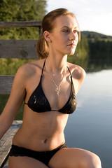 Junge Frau auf einem Steg am See