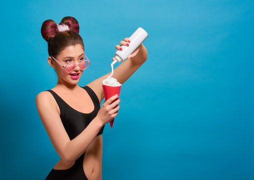 Side view of fancy girl pressing whipped cream in red paper can, looking at camera. Wearing black stylish swimwear, pink eyeglasses, pretty hairstyle with bow. Feeling positive, happy, good.