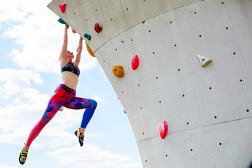 Photo from below of sports girl in leggings hanging on wall for climbing against blue sky