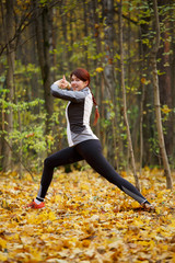 Picture of sports fitness brunette doing stretching exercises at fresh air
