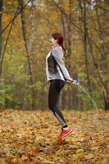 Full-length picture of athlete brunette jumping with rope at autumn forest
