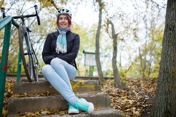 Photo of woman sitting on stairs next to bicycle