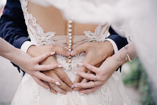 wedding photo of wedding rings on the hands of a couple. heart