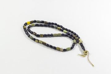 Close-up shot of curved handmade black and green stone islamic prayer beads