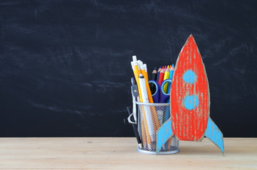 Back to school concept. cardboard rocket and pencils over open book in front of classroom blackboard.