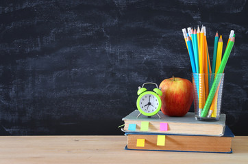 back to school concept. stack of books and pencils over wooden desk in front of blackboard.