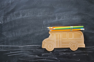 Back to school concept. Top view image school bus and pencils over classroom blackboard background.