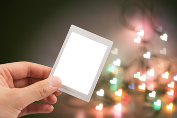 Hand holding instant photo or picture frame with blurred christmas lights background with copy space warm retro vintage tone.