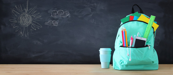 school bag with stationery and notebooks in front of blackboard. Back to school concept.