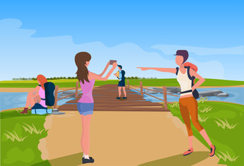 tourist relaxation photographing wooden bridge across river mountain landscape background expedition concept flat vector illustration