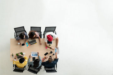 Top view of diverse people of creative team group using smartphone, mobile phone, tablet and computer laptop. Overhead view of asian young creative start up meeting. Have copy space for fill text.