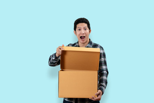 Happy customer asian man excited expression opening and holding box looking at camera with isolated background clipping path feeling surprise and satisfaction. Ordering or buying unbox concept design.