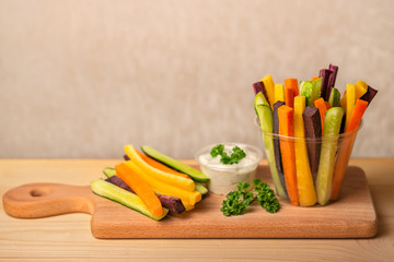 colorful carrots and cucumbers vegetables julienned with sour cream dip on wooden cutting board, concept of healthy eating with copy space
