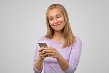 Happy loving girlfriend texting with satisfied expression. Portrait of pleased playful young girl in casual outfit, holding smartphone and smiling broadly, gazing at screen with satisfaction