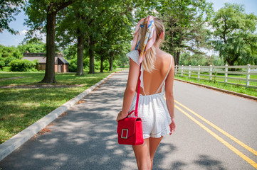 Beautiful fashionable woman walking on the road in summer