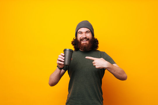 Happy bearded man pointing at mug cup of coffee to go