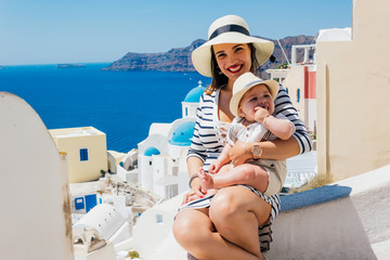 Mother and son enjoying a holiday in Santorini greece, Background the caldera and the famous Santorini volcano