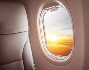Poster Avion à Moteur Airplane interior with window view of sunset above clouds.