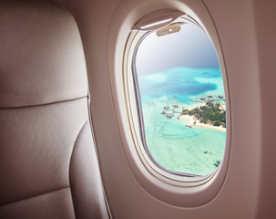 Airplane window with beautiful Maldives island view
