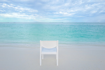Summer concept , White chair on the beach white sand and turquoise sea color at maldives on the weekend holidays