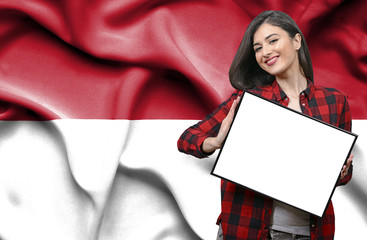 Woman holding blank board against national flag of Monaco