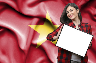 Woman holding blank board against national flag of Vietnam