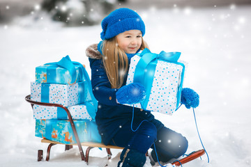 Adorable child with Christmas presents outdoors