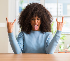 African american woman at home shouting with crazy expression doing rock symbol with hands up. Music star. Heavy concept.