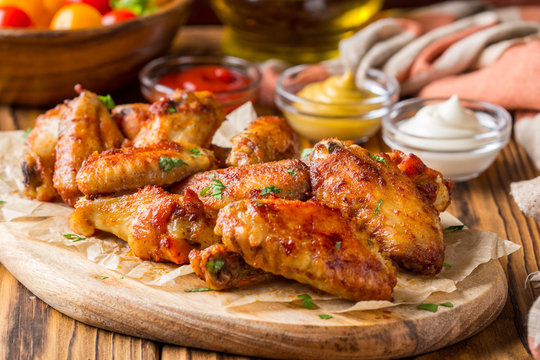 Grilled chicken wings with ketchup and mustard sauces on wooden board. Traditional baked bbq buffalo
