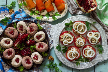Georgian cuisine. Fresh homemade Rolls of peppers stuffed with nuts, tomatoes and walnut coriander sauce, pkhali bean. Top view flat lay background.