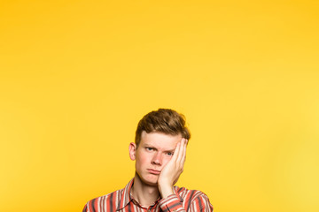 bored disinterested weariful indifferent unenthusiastic man. portrait of a young guy on yellow background popping up or peeking out from the bottom. copy space for advertisement.