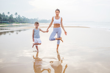 A mother and a son are doing yoga exercises at the seashore of tropic ocean