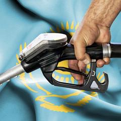Gasoline consumption concept - Hand holding hose against flag of Kazakhstan