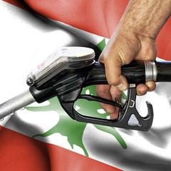 Gasoline consumption concept - Hand holding hose against flag of Lebanon