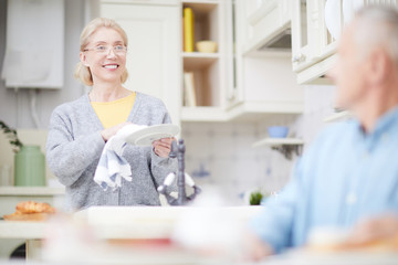 Happy aged housewife drying clean plates with towel in the kitchen and looking at her husband