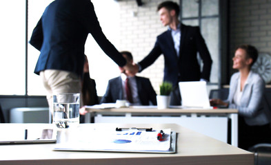 Two confident business man shaking hands during a meeting in the office.