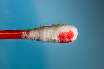 Cotton swab with blood on a blue background