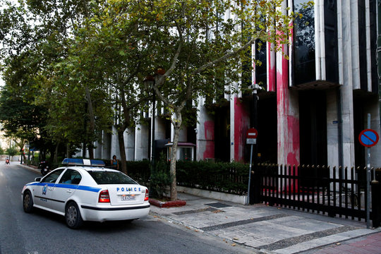 A police car is seen outside the Foreign Ministry building after a Greek self-proclaimed anarchists group threw red paint at the facade of the building, in Athens