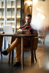Serious man with open book sitting on armchair by table in cafe with laptop in front