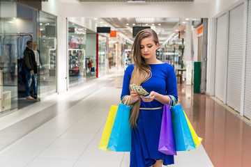 Woman with bags counting dollars for shopping