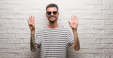 Young adult man wearing sunglasses standing over white brick wall showing and pointing up with fingers number nine while smiling confident and happy.