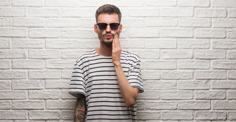 Young adult man wearing sunglasses standing over white brick wall touching mouth with hand with painful expression because of toothache or dental illness on teeth. Dentist concept.