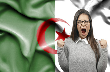 Ecstatic woman holidng fists and screaming against flag of Algeria