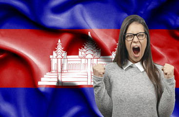 Ecstatic woman holidng fists and screaming against flag of Cambodia