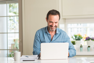 Middle age man using laptop at home with a happy face standing and smiling with a confident smile showing teeth