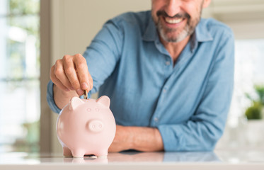 Middle age man save money on piggy bank with a happy face standing and smiling with a confident smile showing teeth