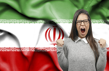 Ecstatic woman holidng fists and screaming against flag of Iran