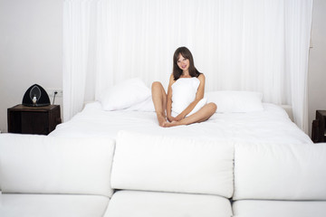 Young smiling woman on white sofa