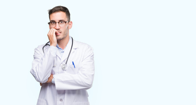 Handsome young doctor man looking stressed and nervous with hands on mouth biting nails. Anxiety problem.